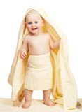 The cheerful baby costs wrapped up in yellow towel Stock Photography