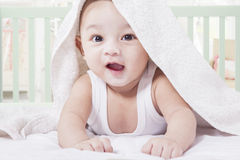 Cheerful baby crawling on bed Stock Images