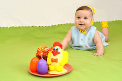The cheerful baby with an easter entertainment on a green background Royalty Free Stock Images