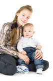 Cheerful baby and the elder sister hug Stock Photos