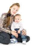 Cheerful baby and the elder sister hug Royalty Free Stock Image