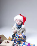Cheerful  baby  with gift boxes wearing santa hat Stock Photo