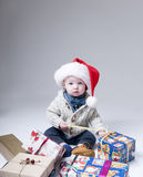 Cheerful  baby  with gift boxes wearing santa hat Stock Images