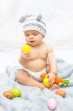 Cheerful baby girl in bunny hat gray blanket Royalty Free Stock Image