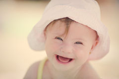 Cheerful  baby girl with Downs Syndrome playing in the pool. Cheerful little baby girl with Downs Syndrome playing in the pool Stock Photos