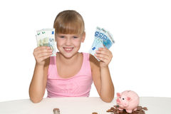 Cheerful baby girl with money in her hands  isolated. Happy baby girl with money in her hands and piggy bank  on the table isolated Stock Images