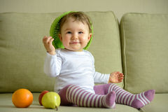 Cheerful baby girl plays with dish and fruit Royalty Free Stock Photography