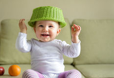 Cheerful baby girl plays with dish and fruit Stock Image