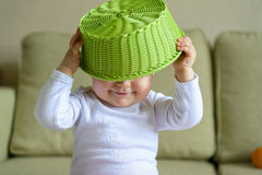 Cheerful baby girl plays with fruit dish Stock Photo