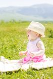 Cheerful baby girl is sitting on the grass Royalty Free Stock Image