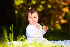 Cheerful baby girl sitting on the green grass in the city park at summer day. Royalty Free Stock Images