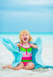 Cheerful baby girl in towel sitting on beach Royalty Free Stock Photo
