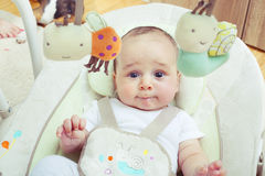 Cheerful baby in his swing Royalty Free Stock Photo