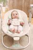 Cheerful baby in his swing Royalty Free Stock Photography