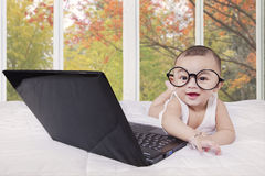 Cheerful baby and laughing with laptop Stock Image