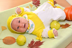 The cheerful baby lies among autumn leaves and fruit Royalty Free Stock Images