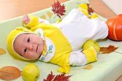 The cheerful baby lies among autumn leaves and fruit Stock Images