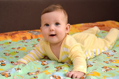 The cheerful baby lies on a stomach. A portrait Stock Images