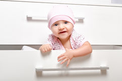 Cheerful baby looking out of the the chest of drawers. Portrait of a cheerful baby looking out of the the children's chest of drawers Stock Photos