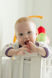 Cheerful baby looking out of his bed Stock Images