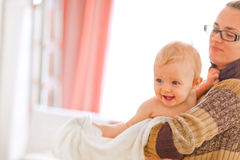 Cheerful baby on mamas arms looking in corner Royalty Free Stock Images