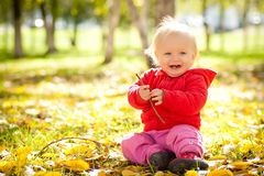 Cheerful baby play with wooden branch in park Royalty Free Stock Photo