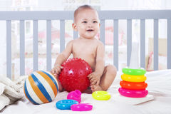 Cheerful baby playing with toys in baby crib Stock Photos