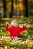 Cheerful baby in a red dress playing with yellow Royalty Free Stock Photo