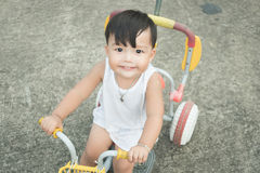 Cheerful of baby riding small bicycle and looking at camera on c royalty free stock image