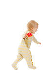 Cheerful baby running with rattle Royalty Free Stock Image