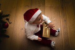 Cheerful baby in Santa hat with present box royalty free stock photo