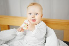 Cheerful baby sits on bed and holds rattle. Cute cheerful baby with big light eyes and blond hair sits on bed in playful mood and holds rattle in form of flower Stock Photos