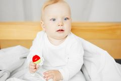 Cheerful baby sits on bed and holds rattle. Cute cheerful baby with big light eyes and blond hair sits on bed in playful mood and holds rattle in form of flower Royalty Free Stock Image