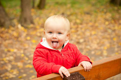 Cheerful baby stay on wood bench Stock Photography