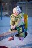 Cheerful baby swinging on playground Stock Image