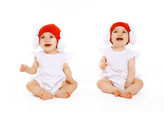 Cheerful baby twins in hats. Having fun Stock Photos