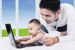 Cheerful baby typing on laptop with dad Royalty Free Stock Image