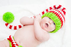 Cheerful Baby Wearing Cute Knit Hat. Cheerful baby wearing red white and green striped knit hat Royalty Free Stock Photo