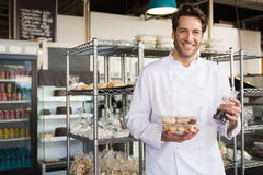 Cheerful baker holding coffee house and food Stock Photo