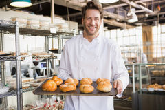 Cheerful baker holding tray of bread Stock Images