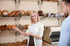 Cheerful baker is proposing wide assortment of Stock Images