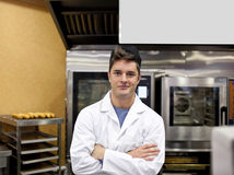Cheerful baker standing in his kitchen Stock Photography