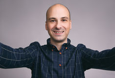Cheerful bald man taking selfie. Close up portrait of a cheerful bald man taking selfie over gray background royalty free stock photos