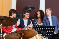 Cheerful Band Members Performing Together. Cheerful multiethnic band members performing together in recording studio Royalty Free Stock Image