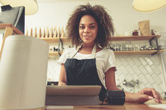 Cheerful barista delivering account to client Royalty Free Stock Photos