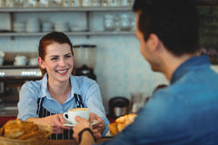 Cheerful barista giving coffee to customer at cafeteria. Cheerful female barista giving coffee to customer at cafeteria Stock Photos