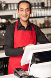Cheerful barista staff at the cash counter. Asian barista staff at the cash counter confirming order Royalty Free Stock Images