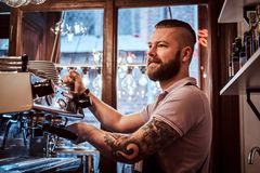 Smiling barista with stylish beard and hairstyle making coffee for a customer in the coffee shop. Cheerful barista with stylish beard and hairstyle making coffee stock images