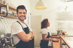 Cheerful barista working at counter in cafe Stock Photography