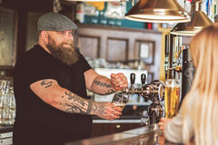Cheerful bartender filling mug of cold lager in pub Royalty Free Stock Photos